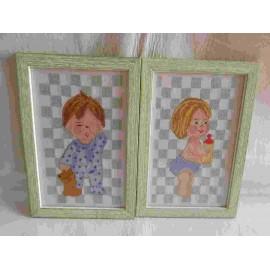 Pareja de cuadros enmarcados realizados a punto de cruz de niño y niña para habitación infantil.